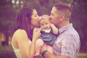 父親と母親にキスをされている女の子の赤ちゃん