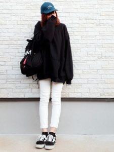 黒いオーバーサイズのパーカーを着た女性