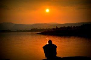 夕陽が差す湖に座る男性の後ろ姿