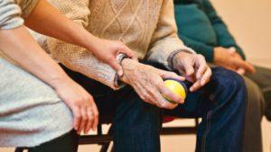 ボールを持った老人の手を優しく握る手