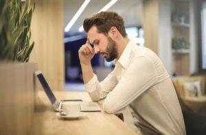 パソコンを眺め考える男性