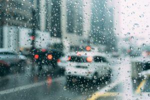 雨粒がついた窓から見える車の列