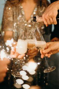 シャンパンを注ぎグラスを合わせる人々の手元