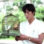 鳥籠を見つめる豊川悦司