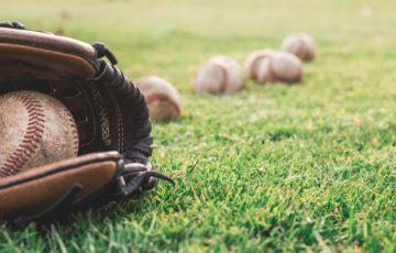 芝生の上に転がった野球のグローブとボール