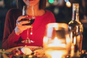 ワインを片手にディナーを楽しむ女性の姿