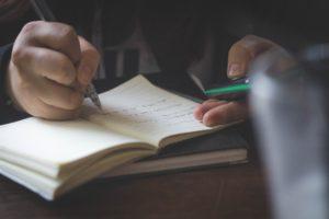 ノートにメモを取る人の手