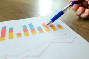 カラフルな棒グラフを指すボールペンを持つ手