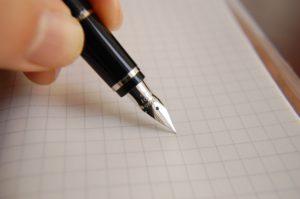 署名をする為にペンを持つ人の手