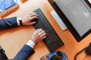 スーツ姿でパソコンのキーボードをタイプする男性の手元