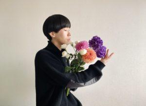 花束を抱える坂口涼太郎の横姿