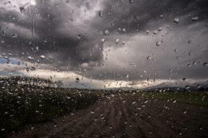 黒い雨雲と車のフロントラインに付いた雨粒