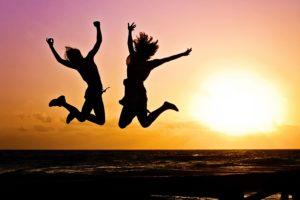 ビーチでジャンプする2人の女性のシルエット