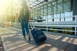 旅行バッグを持って歩く女性の後ろ姿
