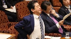 腰に手を当て背を伸ばす安倍首相