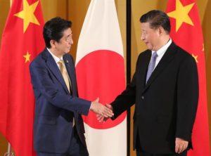 握手をする安倍首相と習近平