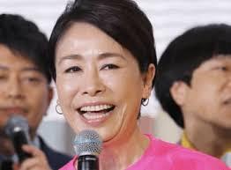 ピンクの服を着てマイクを持つ笑顔の安藤優子