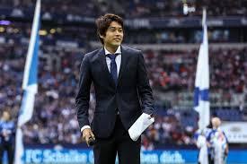 サッカーコートをスーツで歩く内田篤人