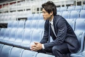 サッカー場のベンチに座る内田篤人