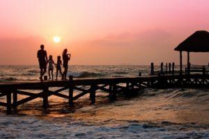 夕焼けに照らされる4人の家族のシルエット