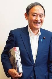 本を腕に挟む菅義偉官房長官