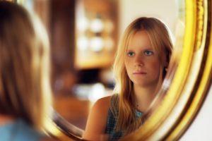 鏡に映る真顔の女性