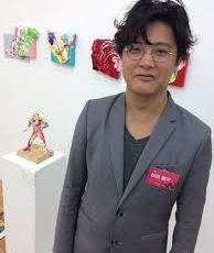 自身の作品の隣に立つ杉田陽平