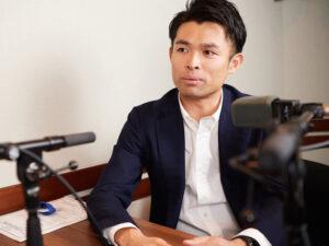 マイクの前に座る豊田剛一郎