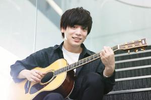 ギターを演奏する笑顔の優里